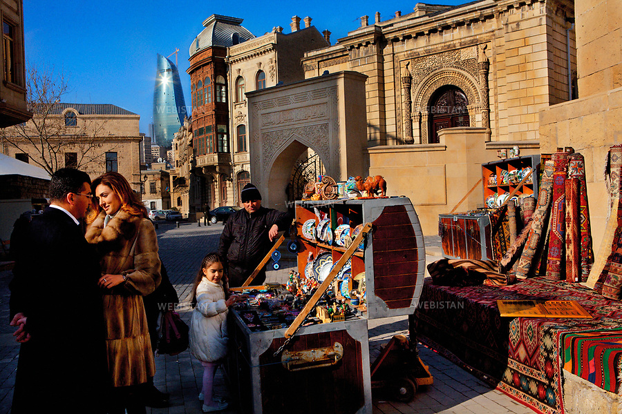 Azerbaijan, Baku, Old City, March 26, 2012<br /> An Azerbaijani couple is posing for a video-clip in the Old City of Baku with their daughter. They stop at an open-air shop to look at souvenirs. In the distance, one of the three Flame Towers, a striking new addition to the skyline of Baku, rises from beyond the Old City walls.<br /> <br /> Azerba&iuml;djan, Bakou, Vieille Ville, 26 mars 2012 <br /> Un couple azerba&iuml;djanais pose pour un clip vid&eacute;o, dans la Vieille Ville de Bakou avec leur fille. Ils s&rsquo;arr&ecirc;tent devant l&rsquo;&eacute;tal de souvenirs. Au loin, on aper&ccedil;oit la pointe de l&rsquo;une des trois tours des &quot;Flame Towers&quot; derri&egrave;re l&rsquo;enceinte de la Vieille Ville.