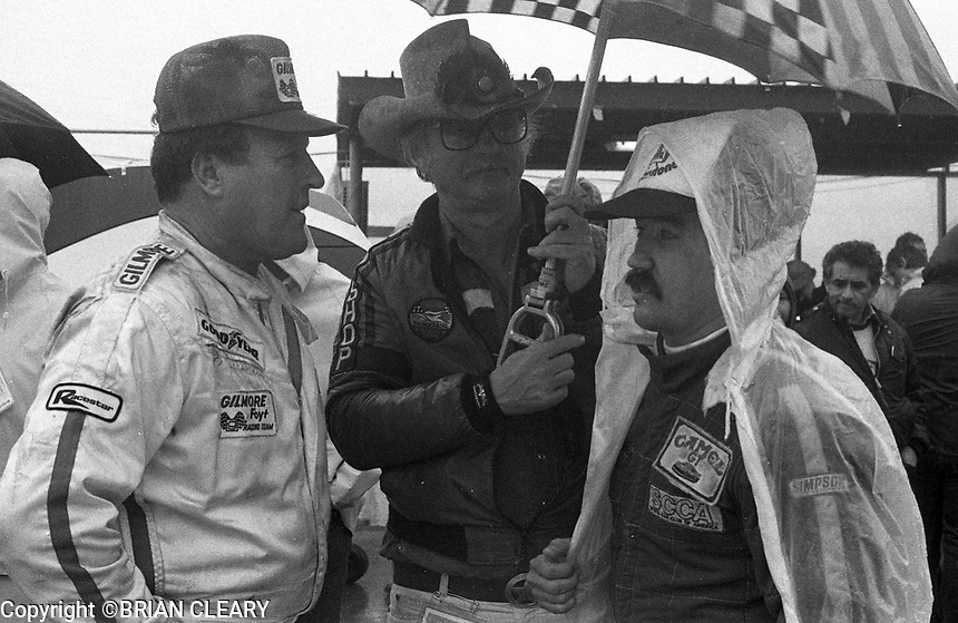 Let to right:  A.J. Foyt, Jr, Preston Henn and Randy Lanier wait out a red flag in the rain at the 1983 24 Hours of Daytona , Daytona Internationa Speedway, Daytona Beach, FL, February 1-2, 1983.  (Photo by Brian Cleary / www.bcpix.com)