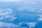 The Channel, England. Aerial view of wind turbines in the sea seen through clouds.