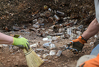 """NWA Democrat-Gazette/CHARLIE KAIJO Gardner Susan Benson and volunteer Bruce Wright of Eureka Springs (from left) excavate a trash dump, Thursday, April 11, 2019 behind the Crescent Hotel in Eureka Springs. <br /><br />An old trash dump has been discovered behind the Crescent Hotel in Eureka Springs. It contains hundreds of bottles dating from the late 1930s, when the building was a """"cancer"""" hospital run by a quack doctor named Norman Baker. A team of archeologists from the University of Arkansas studied the site and revealed what they found."""