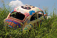 Volkswagen beetle sedan with colorful custom paint job abandoned in a weed covered field along Hwy 287 in Texas.