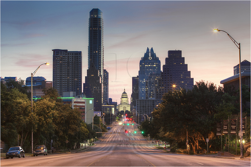 This landscape image of the Texas State Capitol building looks down the famous Congress Avenue. The Austonian and Frost Tower rise in the distance on this early morning in Austin.
