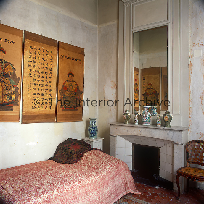 A traditional bedroom with a distressed plaster finish on the walls and a plain marble fireplace with a tiled hearth. The room is furnished with a single bed with a pink floral pattern cover and a cane backed chair. Chinese scrolls hang on the walls and Chinese pots are displayed on the mantelpiece