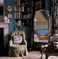 A cheval mirror and a green bucket chair in the corner of the spare bedroom