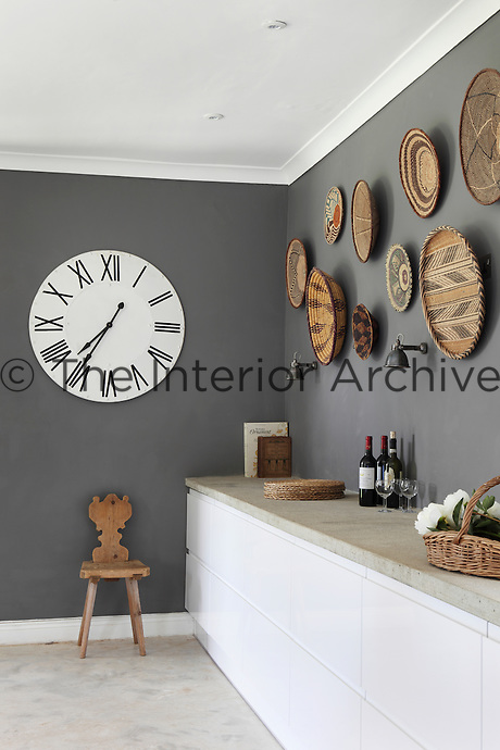 A collection of African woven bowls creates a contrasting display of pattern against the grey walls in the kitchen