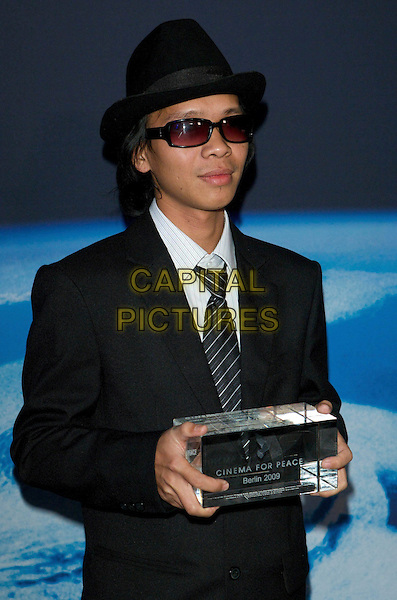 AUNG HTUN.Cinema for Peace 2009, Konzerthaus, Gendarmenmarkt, Berlin, Germany..February 9th, 2009.half length black suit jacket hat sunglasses shades award trophy .CAP/PPG/JH.©Jens Hartmann/People Picture/Capital Picturess