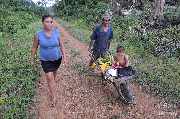 Two-year old Fabiana Souza da Silva gets a ride in a wheelbarrow from her father, Joao Luis Santos Borge da Silva, while her mother, Maria Benedita de Chaga Sousa, walks beside them. The family lives on the Esperança Sustainable Development Project, near Anapu in the northern Brazilian stte of Para, where U.S. Catholic Sister Dorothy Stang was murdered for her defense of the jungle and the landless poor.