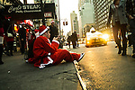 NEW YORK, NY - DECEMBER 15: Revelers dressed as Santa Claus sit on the street to rest during the annual SantaCon event December 15, 2012 in New York City. (Photo by Donald Bowers)