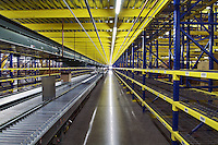 Interior waehouse, long conveyor belt moving freight under large storage racks.