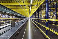 Interior waehouse, long conveyor belt moving freight under large storage racks.