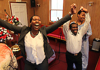 From left, Immacule Nyirabeza calls out to Jesus next to Derrick Muchembe and Emmy Gitugu during Sunday service at The Africa Lighthouse Baptist Temple near Stony Point in Albemarle County, VA. The small 10 family congregation is made up of African refugees and immigrants who's service is spoken in Swahili and translated into English. They've just signed a rent-own lease for a small church after meeting for three years at a local school. Photo/The Daily Progress/Andrew Shurtleff