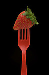 Strawberry on a red fork.