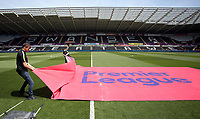 Premier League staff lay a banner on the pitch prior to the Premier League match between Swansea City and West Bromwich Albion at The Liberty Stadium, Swansea, Wales, UK. Sunday 21 May 2017