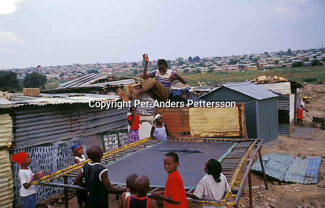 DIEPSLOOT, SOUTH AFRICA - FEBRUARY 29: Unidentified children play on a trampoline on February 29, 2004 in Diepsloot a township outside Johannesburg, South Africa. Diepsloot is the fastest growing township around Johannesburg as rural South Africans come to Johannesburg to look for work. They face difficulties finding work and housing. Many illegal immigrants from other African countries live in Diepsloot and some of the residents complain that corrupt officials give foreigners with money houses quickly. South Africa faces a backlog of 6-7 million houses and they have built around 1,7 million houses since coming to power in 1994. .(Photo: Per-Anders Pettersson/Getty Images).........