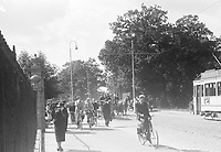 Photo from the Photo from the NIOD's Huizinga collection. Busy street with pedestrians, cyclists, a tram and a highly charged car with household goods.