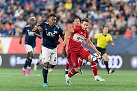 FOXBOROUGH, MA - AUGUST 25: Przemyslaw Frankowski #11 of Chicago Fire attempts to control the ball as DeJuan Jones #24 of New England Revolution pressures during a game between Chicago Fire and New England Revolution at Gillette Stadium on August 24, 2019 in Foxborough, Massachusetts.