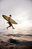 INDONESIA, Mentawai Islands, Kandui Surf Resort, surfer jumping into the Indian Ocean with surfboard