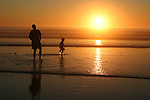 Man and child watching sunset at Carmel beach