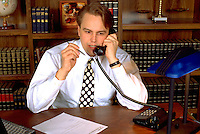 Lawyer age 27 on the telephone in office.  St Paul Minnesota USA