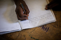A student writes in her notebook while attending class in the compound of the Cluster resource Center of Lafaissa, Somali Region, Ethiopia on Monday November 9 2009. .The Lafaissa facility is supported by the British non governmental organization Save the Children UK..