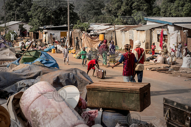 People's belongings piled up in a street in a Muslim district of the capital that is under the protection of the French army. The residents wait to be evactuated but many of the men have armed themselves against any incursions by those seeking to attack them while they wait. In 2013 a rebellion by a predominantly Muslim rebel group Seleka, led by Michel Djotodia, toppled the government of President Francios Bozize. Djotodia declared that Seleka would be disbanded but as law and order collapsed the ex-Seleka fighters roamed the country committing atrocities against the civilian population. In response a vigillante group, calling themselves Anti-Balaka (Anti-Machete), sought to defend their lives and property but they then began to take reprisals against the Muslim population and the conflict became increasingly sectarian. French and Chadian peacekeeping forces have struggled to contain the situation and the smaller Muslim population began to flee the country.
