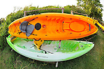 Kayaks, bright orange and green plastic, stored on wood racks at Norman J. Levy Park and Preserve for use on their marshland waterway, at Merrick, New York, USA, 2011 NOTE: 180 degree fisheye lens view. EDITORIAL USE ONLY