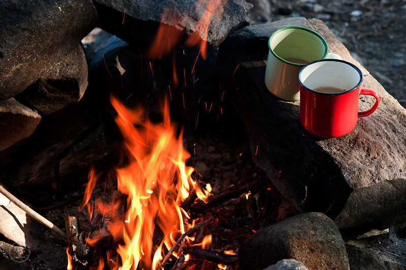 Camp tea in enamel mugs and a blaxing campfire by in Killarney Provincial Park, Onatario, Canada