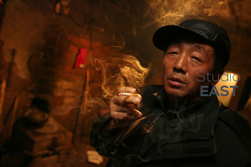 Farmer Liu Dongqing smokes a cigarette in a two-room mud house in Yongfu, on February 27, 2006. Liu said he must pay 2,700 yuan for the right to farm his land this year, a third of the 7,000 yuan to 8,000 yuan he expects to make. That will leave Liu and his wife the equivalent of less than $1 a day each to live on. The increase in fees has forced the couple to cut down to two meals a day, Liu said. Photo by Lucas Schifres/Pictobank