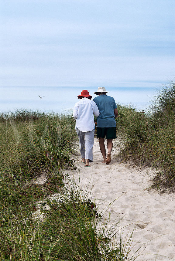 Mature couple walking a dune path to the beach, Cape Cod, Massachusetts, USA