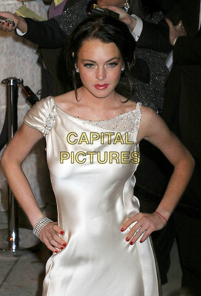 LINDSAY LOHAN.2006 Vanity Fair Oscar Party held at Morton's, West Hollywood, California, USA, 05 March 2006..oscars half length white satin dress red nails hands on hips kabbalah bracelet.Ref: ADM/RE.www.capitalpictures.com.sales@capitalpictures.com.©Russ Elliot/AdMedia/Capital Pictures.