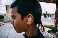 Jason, 11, on a street of Ebeye with a coin in his ear.