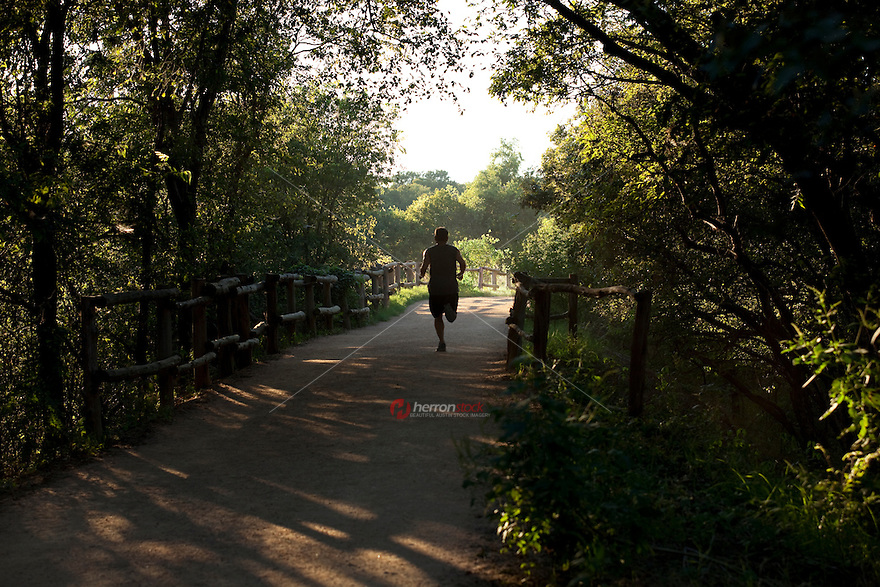 A Determined Runner navigates the gravel pathway along the Hike and Bike Trail on Town Lake