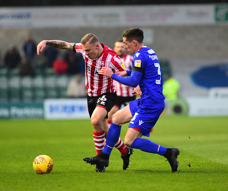 Lincoln City's Harry Anderson vies for possession with Morecambe's Luke Conlan<br /> <br /> Photographer Andrew Vaughan/CameraSport<br /> <br /> The EFL Sky Bet League Two - Saturday 15th December 2018 - Lincoln City v Morecambe - Sincil Bank - Lincoln<br /> <br /> World Copyright © 2018 CameraSport. All rights reserved. 43 Linden Ave. Countesthorpe. Leicester. England. LE8 5PG - Tel: +44 (0) 116 277 4147 - admin@camerasport.com - www.camerasport.com