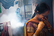 Women cover their face while a civic worker fumigates their apartment   to prevent the spread of malaria and dengue fever in New Delhi, India.