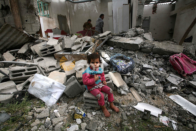 A Palestinian child sit in front of their house, destroyed after an Israeli air strike in Jabalya in the northern Gaza Strip. A recent wave of Israel bombings have reported to have killed at least 20. Photo by Ashraf Amra