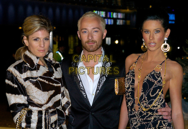 "HOFIT GOLAN, SCOTT HENSHALL & JASMINE LENNARD.At the UK Film Premiere of ""The Holiday"", Odeon Leicester Square, London, UK..December 5th 2006.half length black white animal print coat jacket gold necklace earrings hoop jewellery.CAP/CAN.©Can Nguyen/Capital Pictures"