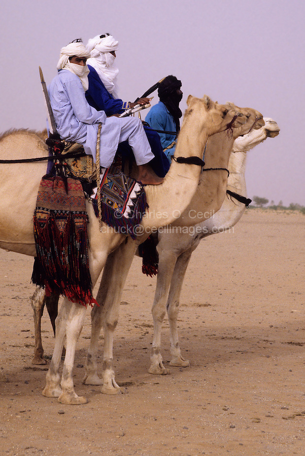 In-Gall, near Agadez, Niger - Tuaregs on Camels at Annual Cure Salé, Annual Gathering of Tuareg Nomads.  As is their custom, most of the men cover their mouths with the tagulmust, the Tuareg veil.  Note camel blanket and other decorations.