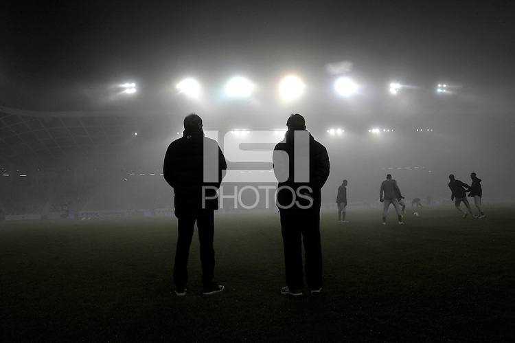 Jurgen Klinsmann (left), coach of team USA, standing in the fog to watch the team warm up before the friendly match Slovenia against USA at the Stozice Stadium in Ljubljana, Slovenia on November 15th, 2011.