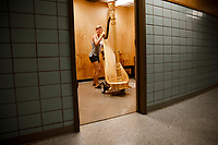 Volunteer Chelsea Balmer moves a harp from a practice room during the 11th USA International Harp Competition at Indiana University in Bloomington, Indiana on Wednesday, July 3, 2019. (Photo by James Brosher)