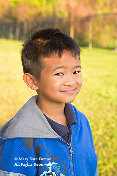 One second grade Vietnamese American boy poses on school ground for portrait outdoors-model released