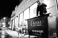 "Adam Weissman, self described ""freegan"", rummages through a dumpster near a supermarket in New York City on April 5, 2006."