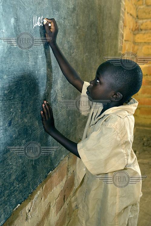 A schoolboy writes with chalk on a blackboard at the Leweme School.
