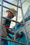 HURGHADA - EGYPT - 03 March 2015 -- Boy removing paint from  the side of a wooden boat at ship yard. -- Photo: Kimmo HAGMAN / EUP-IMAGES
