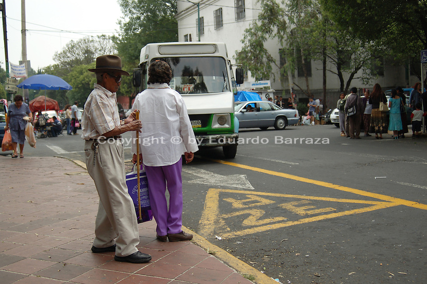 """Coyoacan, Mexico City - A street scene shows in Coyoacan shows some residents getting ready to board a bus near Plaza Coyoacan.  Coyoacan's name comes from Nahuatl it likely meaning """"place of coyotes"""".  Hernán Cortes and the Spanish conquistadors used this area as a headquarters during the Spanish conquest of the Aztec Empire. They also made it the first capital of New Spain between 1521 and 1523.  In recent times, has been a counterculture hotbed and where Frida Kahlo and Diego Rivera lived, a few blocks away from Leon Trotsky.  Due the historic and cultural relevance, their homes are now the Frida Kahlo Museum and the Leon Trotsky Museum, which are visited by thousands of tourists every year.  Modern-day Coyoacan is a quiet residential area with cobblestone streets, restaurants, parks, squares, and a favorite hangout for bohemia enthusiasts. Photo by Eduardo Barraza © Copyright"""