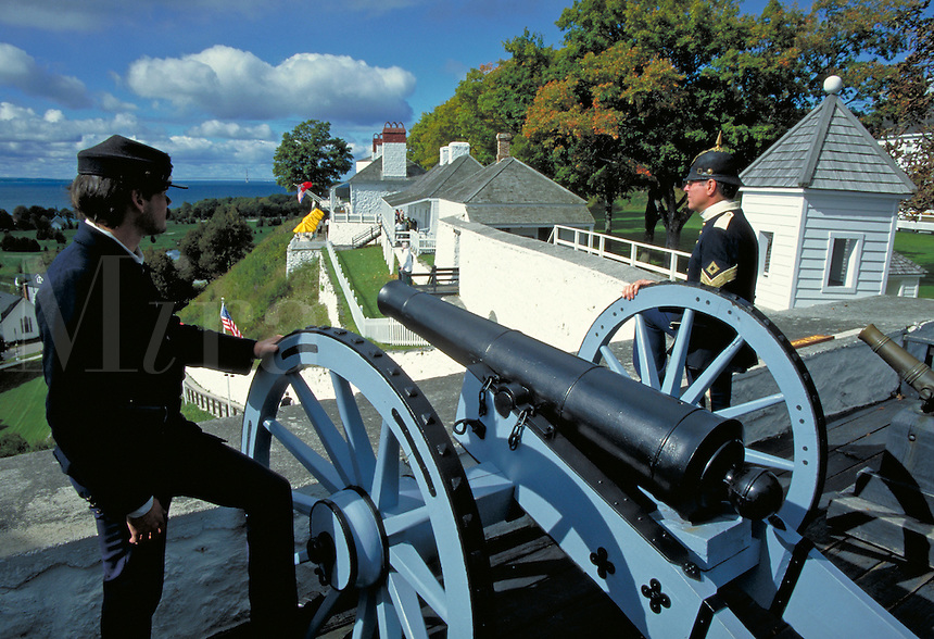 Interpretive guides dressed in Civil War era uniforms with cannon on wall of fort, artillery. Mackinac Island Michigan USA.