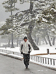 February 14, 2014, Tokyo, Japan - A lone jogger braves the falling snow on the Imperial Palace outer garden in Tokyo on Friday, February 14, 2014. Two weeks in a row, the nation's capital was blanketed with inches of snow as a low-pressure front hit a wide swath along the Pacific coasts, disrupting land, sea and air transportation services.  (Photo by Natsuki Sakai/AFLO)