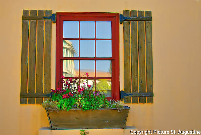 Photograph of red window with reflection, shutters and flower box