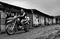 A Brazilian woman on a motorbike passes through the unpaved, muddy street in a small river community Sao Paulo de Olivenca, Brazil, 22 April 2004. Amazonia is the world's largest dense tropical forest area. Since the 16th century the original indigenous people have been virtually pushed away or exterminated. The primal ancient unity between tribes and the jungle ambient has changed into a fight between the urban based civilization and the jungle enviroment. Although new generations of white and mestizo settlers have not become adapted to the wild tropical climate and rough conditions, they keep moving deeper into the virgin forest. The technological expansion causes that Amazonia is changing rapidly.