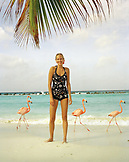 ARUBA, portrait of young woman standing on the beach smiling in the middle of Pink Flamingos, Renaissance Island