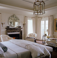 Light floods into this bedroom from French windows accentuating the freshness of the white painted panelling and crisp bedlinen
